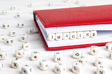 Word Imagine written in wooden blocks in red notebook on white wooden table.