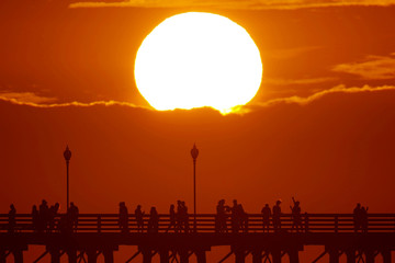 The sun sets behind a cloud as people cool off with a walk along an ocean pier in Oceanside, California