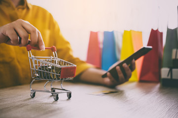 Close up of Shopping Cart, Young woman using smartphone for online shopping website and pay by credit card, Online payment and shopping concept