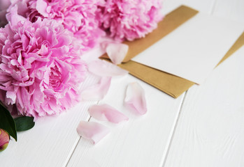invitation card, craft envelope and pink peony flowers