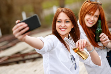 Two women with bottle in hand making selfie together
