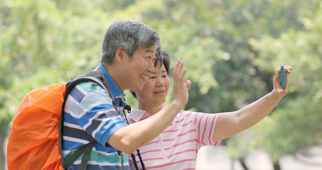Asian old couple taking selfie by mobile phone at outdoor