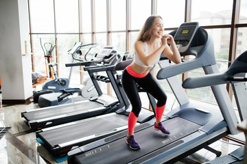 Young girl makes exercises at the gym. Attractive young fitness model runs on a treadmill.
