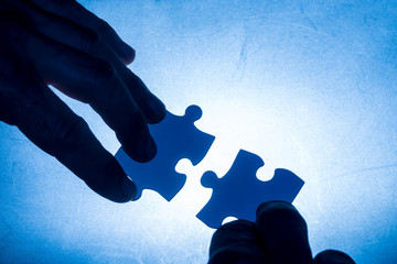 hand moving two blue colored puzzle pieces - blue contact