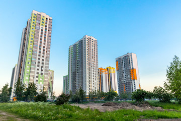 Cityscape on the clear blue sky: bright color high-rise buildings for living