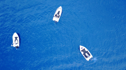 Aerial birds eye view from drone of boats cruising in deep blue sea