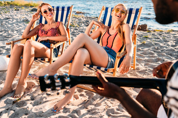 cropped shot of man playing guitar while girls resting in beach chairs