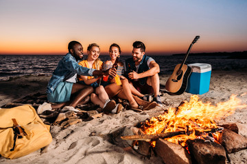 happy multiethnic friends clinking glass bottles with drinks while spending time together on sandy beach at sunset