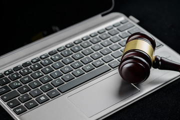 Wooden judges gavel on a computer keyboard. Cyber law and crime
