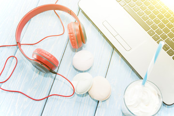 open laptop with white Cup of coffee, marshmallows and red headphones.