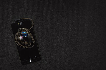 Top view smartphone with headphones on black background.
