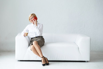 Confident blonde businesswoman sitting on the white stylish leather sofa holding cup of coffee and talking via smartphone, relax breaktime on working day in the rest room