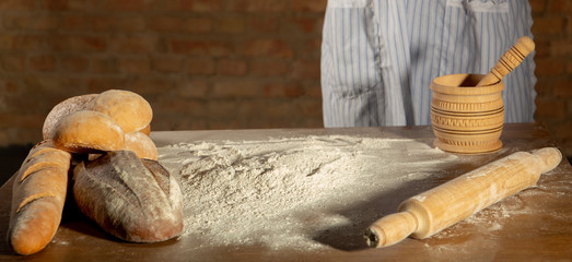 A girl in an apron put a rolling pin, a pot, bread and bun on a table with flour for to make a dough on a brick background