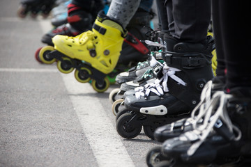 Close up view of wheels befor skating.Legs in rollskikovye skates are lined up in a row