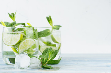 Tropical fresh cold cocktail gin tonic with mint, lime, ice, straw on light blue shabby wood board and white background, copy space.