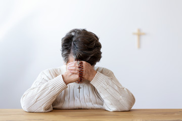 Catholic senior woman praying with rosary in the church