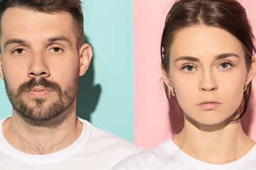 The serious man and woman looking at camera against pink and blue background.