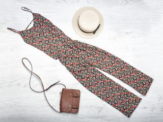 Fashionable concept. Female summer wardrobe. Straw hat, overalls, handbag. Top view