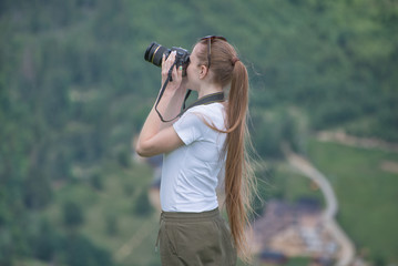Girl with camera stands on a hill and photographing nature. Forest on background