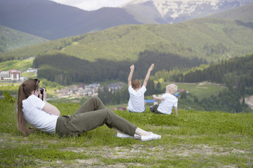 Young woman taking pictures of two young boys. Back view. Mountains on the background.