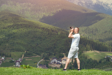 Man with camera standing on a hill and photography nature. Summer day