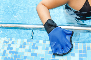 Woman hand wearing gloves for aqua aerobics in swimming pool