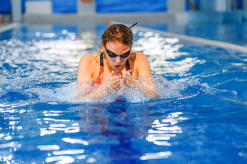Young athlete woman exercising in a blue water of fitness gym swimming pool.
