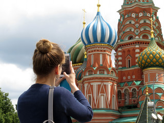 Woman tourist taking pictures with smartphone the St. Basil's cathedral on Red square in Moscow. Tourism in Russia