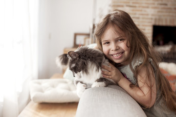 little girl and cat at home on the couch. A happy child and a pet. Copy space