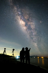 Couple photographer standing near the camera and looking milky way and stars on the sky at night.silhouette style.