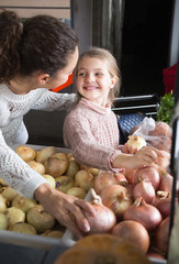 portret of young woman with beautiful daughter choosing onions at store