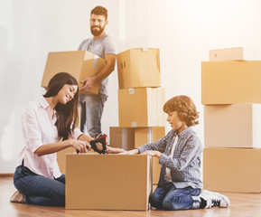 Family Moving to New Place and Packing Boxes.