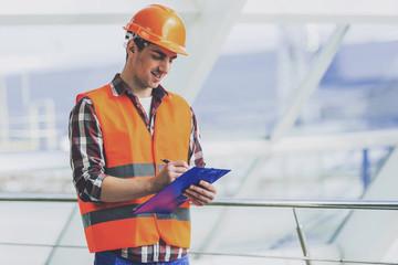 Industrial Engineer in Yellow Helmet Make Notes.