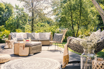 Patterned pillow on rattan chair next to sofa on terrace with rug in the garden. Real photo