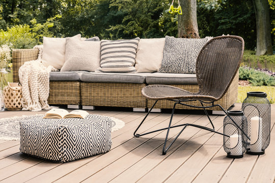 Patterned pouf and rattan chair on wooden patio with pillows on sofa and lanterns. Real photo