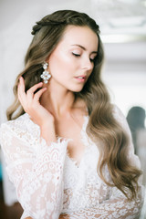 Beautiful young bride with long blond curly hair in a long white lacy dressing gown in the morning at the mirror