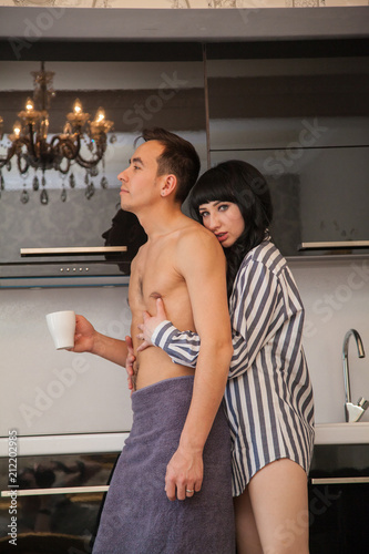 sexy guy and girl in a stylish black kitchen  The girl is brown