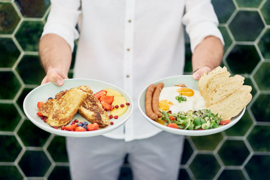 Man holding two plates with delicious breakfast. Chef presenting food in restaurant