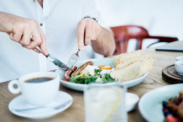 Man having delicious and healthy breakfast in restaurant. Close up of healthy nutritious dish