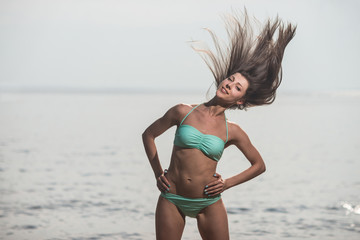 Sexy girl in a swimsuit posing with hair fluttering in the wind