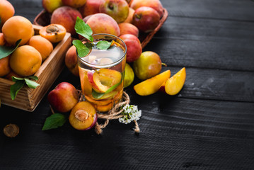 A glass of water with pieces of plums and apricont inside. Copy space. Healthy food, detox