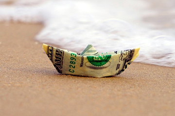 A boat made of paper money in the sea sand A boat out of the dollar in the sea. Sea sand. Concept for the dollar.