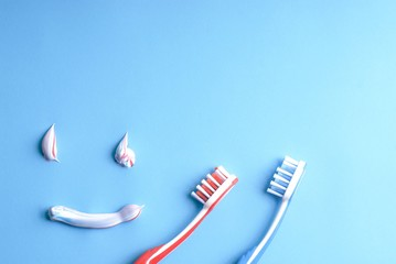 Red and blue toothbrushes and colorful toothpaste shapes