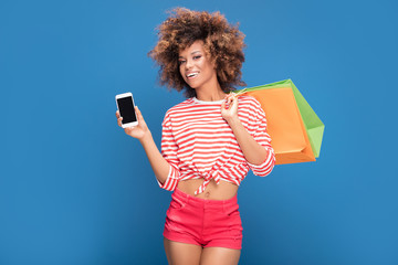 Happy afro girl holding shopping bags and smart phone.