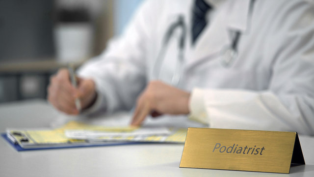 Podiatrist consulting patient online using laptop, keeping medical records