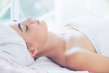 Relaxed young woman lying on spa bed for massage.