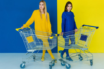 Beautiful brunette and blonde girls posing by shopping carts on blue and yellow background