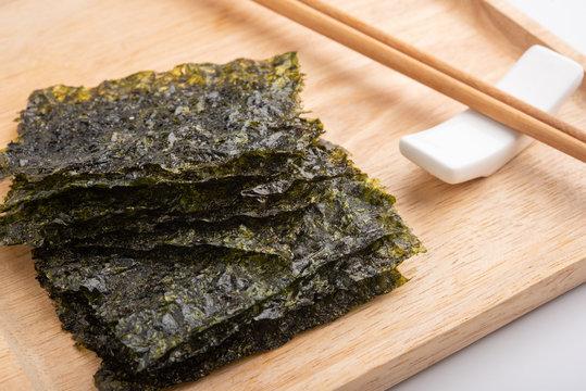 Crispy dried seaweed on wooden plate.