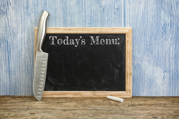 Todays menu written on chalkboard with chef's knife