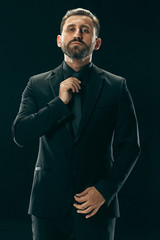 Male beauty concept. Portrait of a fashionable young man with stylish haircut wearing trendy suit posing over black background.